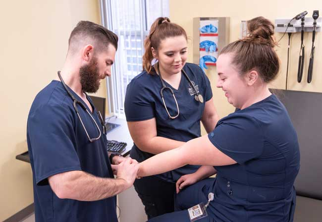 Averett nursing students in a skills lab learning to take each other's pulse on the wrist
